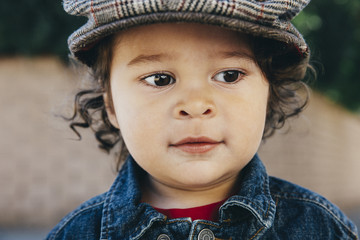 Portrait of a beautiful toddler boy with curly hair