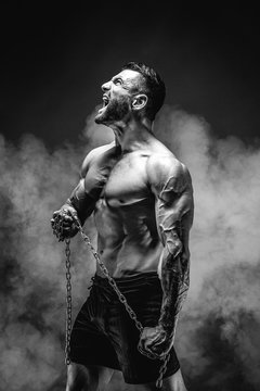Side view of shirtless muscular man screaming and holding chain.