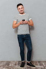 Full length image of smiling man holding smartphone