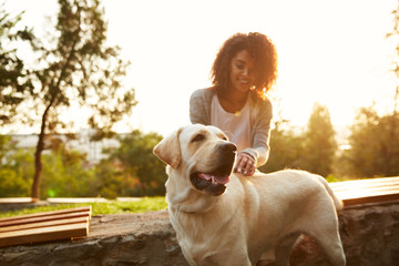 Full-length shot of pretty white dog with owner in park walking