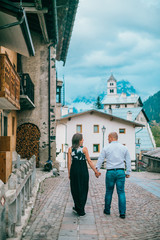 Young couple are walking on an ancient mediterranean street in italy