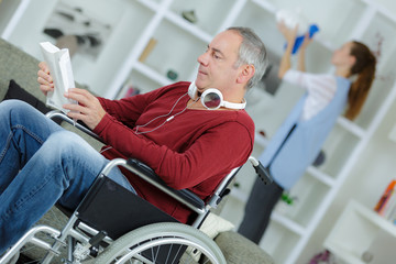 man in wheelchair reading a book