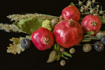 Pomegranate fruits with almonds, nuts and fig berries, dry leaves and reed branches on a black wooden background