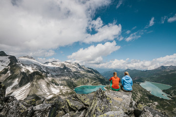 two female hiking friends with colorful outfit sitting in high alpine scenery with a panorama view