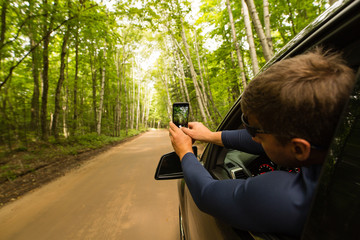 Man in passenger seat of car, taking photograph of view from open car window