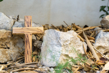 wooden cross with stones and leaves