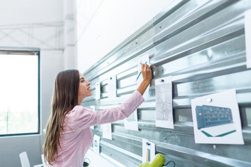 A young brunette is watching notes on the wall attached to a magnet.