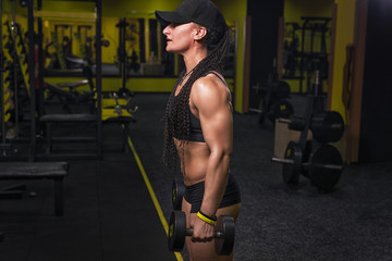 Strong fitness woman bodybuilder in cap and tanned body pumps up the muscles lifting dumbbells in the gym. Fitness woman in the gym. Fitness woman with dumbbell. Panorama 16:9