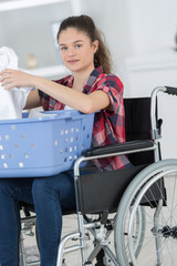 happy woman in wheelchair doing laundry