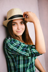 Young woman in hat looking into the camera and smiling