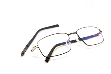 Broken glasses on white background. Eye glasseswith thin metal rim after accident.