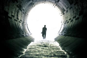 silhouette of man walking in drain tunnel