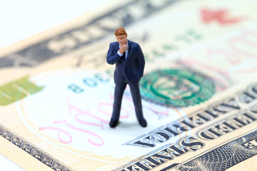 Businessman figurine on usa dollar banknote. Business standing on money concept.