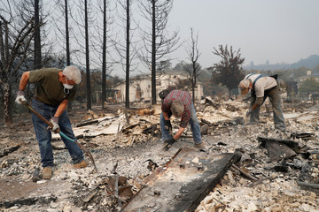 A group of retired police officers works through the ruins to look for a police badge for fellow retired officer Tom Francois after his home was destroyed by the Tubbs Fire in Santa Rosa, California