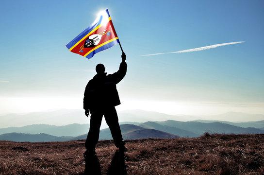 Successful silhouette man winner waving Swaziland flag on top of the mountain peak