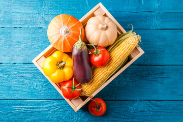 Image from above of wooden box with autumn vegetables