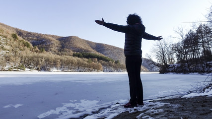 Happy woman in victory pose hands open standing on edge of frozen lake