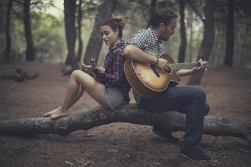 Man and girl sitting in forest playing the guitar and ukulele, Spain