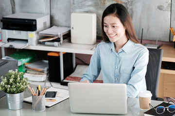 Young asian businesswoman working at office table with smiling face, positive emotion, casual office life concept