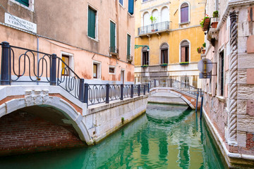 Narrow canal and small bridge in the city of Venice, Italy