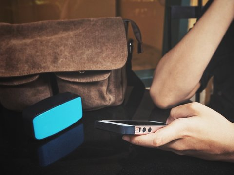 Woman using smart phone with bluetooth speaker