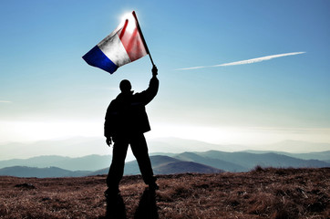 Successful silhouette man winner waving French flag on top of the mountain peak