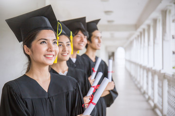 Portrait of young asian man and woman graduates standing in line in front of university building on graduation day