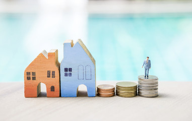 Miniature business man standing on coin stack and wooden house over blurred blue background, real estate and property business concept