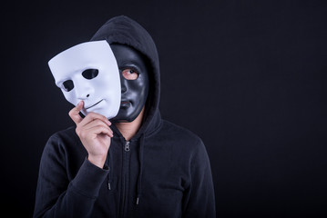 Mystery man wearing black mask holding white mask. Anonymous social masking or halloween concept.