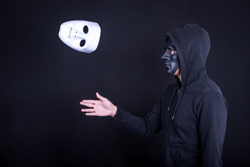 Mystery man holding throwing white mask