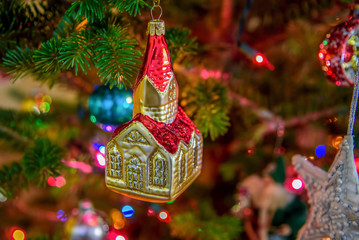 Closeup of vintage style church Christmas ornament and twinkling lights on tree
