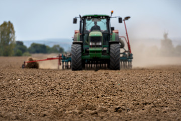 Fototapete - Close-up of crop with Tractor ploughing field in the background. Farmer with tractor seeding.