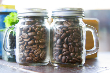 Coffee beans in two bottles placed on the table.