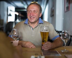 Adult man is enjoying beer with foam