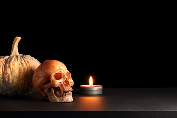 Happy Halloween / smile skull with candle and pumpkin on black table in black background
