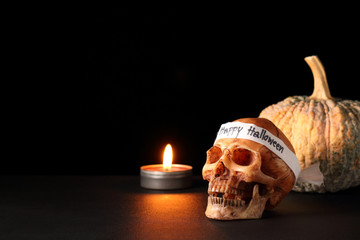 """Happy Halloween / smile skull with candle and pumpkin on black table in black background / skull wearing headband with text """" Happy Halloween """""""