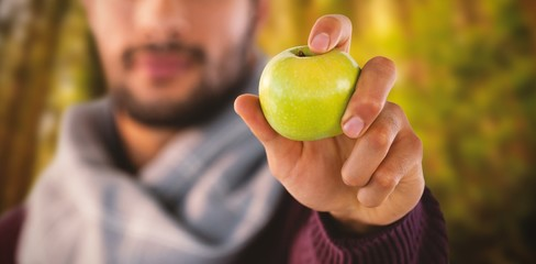 Composite image of man holding apple