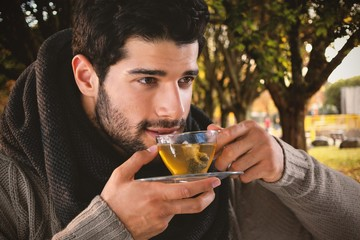 Composite image of thoughtful man having lemon tea