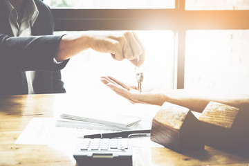 estate agent giving house keys to man and sign agreement on wooden desk in office, Agreement and real estate concept.