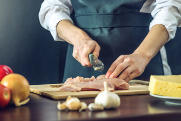 Foto op Canvas Koken The chef in black apron cuts chicken fillet knife. Concept of eco-friendly products for cooking