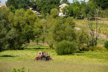 Old red tractor haying in a meadow