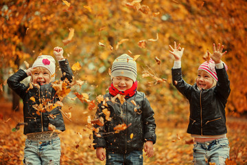 Happy kids having fun with leaves in autumn park