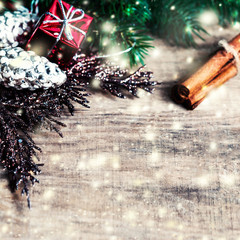 Christmas gifts,  fir tree branches, xmas holiday decorations, festive symbols and falling snow on bright wooden background with copyspace
