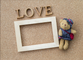 Love text and wooden frame with little cute bear on corckboard background