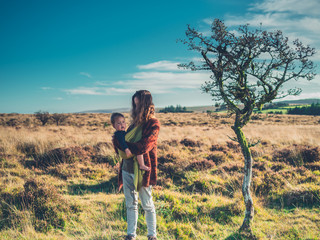 Mother with baby standing by tree in wilderness