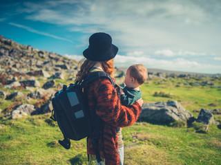Mother with baby trekking in wilderness