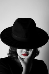 Beautiful young woman wearing black dress, black hat and red lips in the dark concept, Concept : dark, halloween, mysterious, depressed