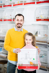 Father and daughter enjoying their purchase of canary bird in pet shop