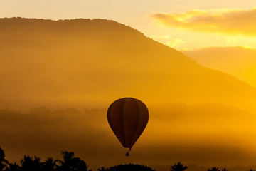 Silhouette of hot air balloon over sunrise with mountain view and fog in morning