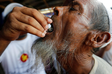 A Rohingya refugee man gets an oral cholera vaccine, distributed by WHO with the help of volunteers and local NGO's, in a refugee camp near Cox's Bazar